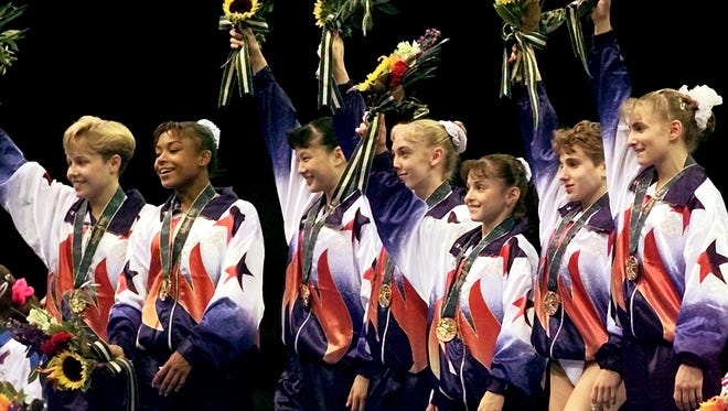 In a file photo from 1996, Team USA gymnasts wave after receiving gold medals in the Olympic team finals in Atlanta. They are from left, Amanda Borden, Dominique Dawes, Amy Chow, Jaycie Phelps, Dominique Moceanu, Kerri Strug, and Shannon Miller.