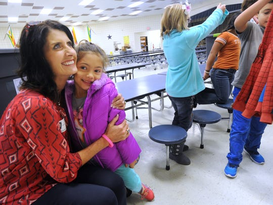 Sophia Cobarruvias, right, hugs Susan Schackmuth, who delivered winter coats for kids at Ortiz Elementary School from the Big Country County Medical Society Alliance Monday.