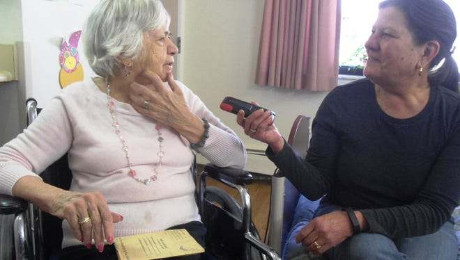 Sandy Hicks Fry plays a Voice-O-Graph message, recorded by her father, on her iPhone as her mother Connie hears it again after more than 60 years.