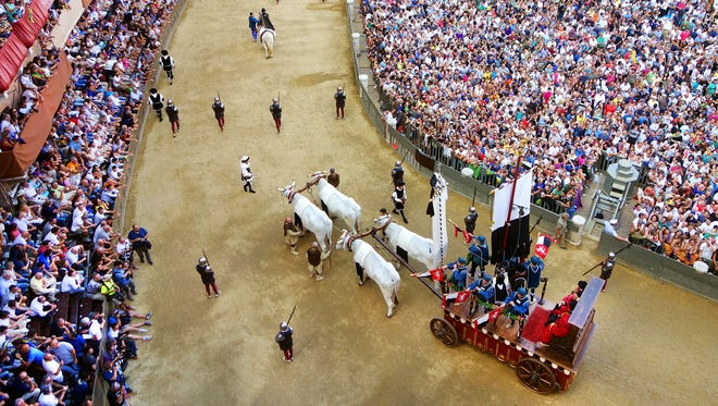 The crowd looks on as an oxen cart pulls the Palio banner through Siena's main square.
