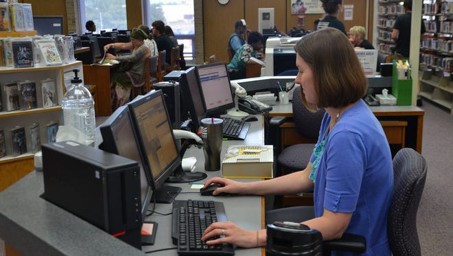 Acquisitions Manager April Dillinger works at a desk on Willard Library's upper floor. The facility is largely funded by a perpetual 2-mill tax.
