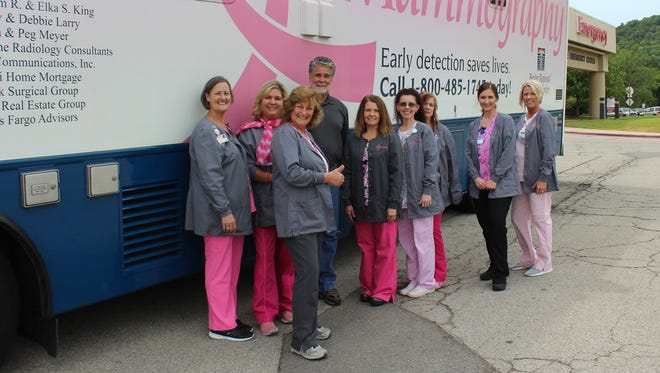 Scott Lumbert of Mountain Home Charter Service with Breast Imaging Center staff members in front of the BRMC Mobile Mammography Unit.