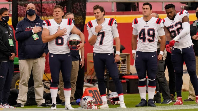 Patriots players stand on the field during the playing of the national anthem before Monday night's game in Kansas City.
