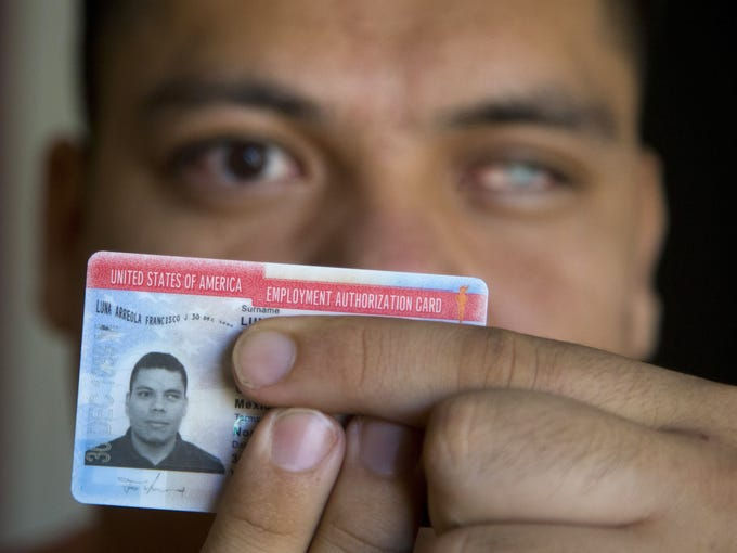 Francisco Luna, 27, holds his DACA card, which allowed