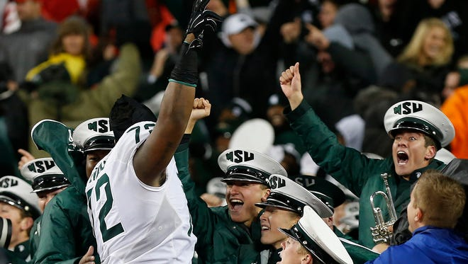 Defensive tackle Craig Evans (72) celebrates with Spartan Marching Band members after MSU's 17-14 victory over Ohio State on Saturday in Columbus, Ohio.