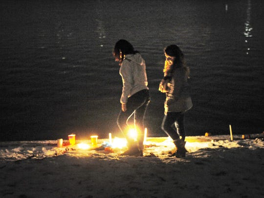 Girls arrive to pay their respects at a memorial constructed on the shore of Morse Lake. Students paid tribute to slain Aubrey Peters with a gathering and balloon launch at Morse Beach Monday night December 9, 2013. Students are seen in the park as the event ended and they were heading back to their cars.