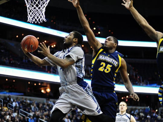 Georgetown Hoyas guard D'Vauntes Smith-Rivera (4) lays the ball up over Marquette Golden Eagles forward Steve Taylor Jr. (25) in the second half at Verizon Center, Jan. 20, 2014.