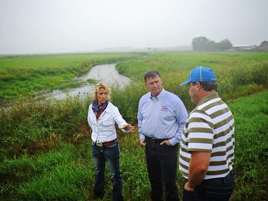 South Dakota State Senator Shantel Krebs, left, talks with Barry Berg, right, watershed coordinator for the Central Big Sioux River Watershed Implementation Project, as Lucas Lentsch, former secretary of agriculture with the South Dakota Department of Agriculture, looks on in an enrolled pasture in the Seasonal Riparian Area Management (SRAM) progam on Skunk Creek near Colton, S.D., on Wednesday, Aug. 6, 2014, during a tour of the different enrolled pastures in the SRAM and Riparian Area Management programs on Skunk Creek and the Big Sioux River. The SRAM program pays farmers to fence livestock away from Skunk Creek's 100-year floodplain from April 1 to Sept. 30.