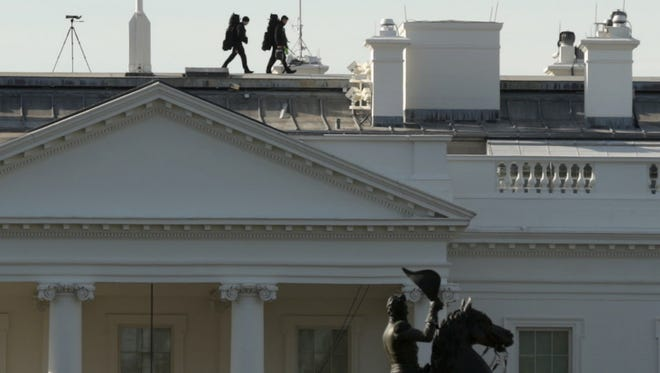 Members of the Secret Service walk along the roof of the White House on Wednesday.