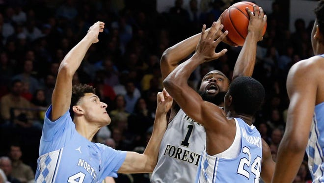 Wake Forest guard Keyshawn Woods (1) shoots the ball while being defended by North Carolina guard Kenny Williams (24) and forward Justin Jackson (44) in the first half.