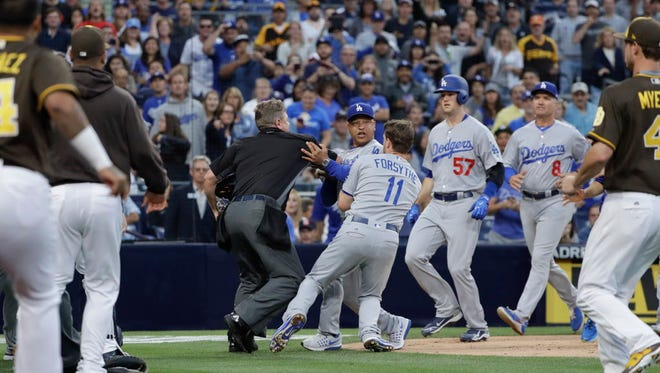 Los Angeles Dodgers manager Dave Roberts, center, is held back by Los Angeles Dodgers third baseman Logan Forsythe (11) as the Dodgers and the San Diego Padres come onto the field during an argument during the second inning of a baseball game Friday, June 30, 2017, in San Diego.