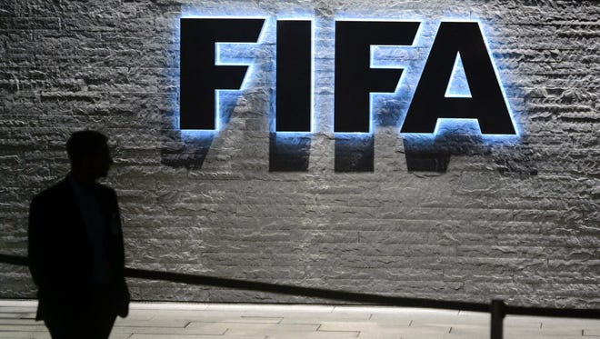 A FIFA employee walks past a sign of the FIFA at the headquarters in Zurich.