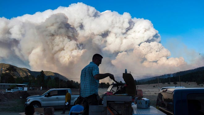 In this May 31, 2018 photo provided by Taosnews.com, faculty of Cimarron Municipal Schools cook hot dogs and chicken for first responders on the scene of the Ute Park Fire from the back of a pickup truck at the intersection of Hummingbird Lane and U.S. Highway 64 in Ute Park, N.M. Evacuation centers have been set up in northeastern New Mexico as heavy smoke from a wildfire has forced residents from Cimarron and the surrounding areas to leave their homes. Authorities were directing people to the communities of Springer and Raton as conditions were expected to worsen Friday, June 1, 2018.