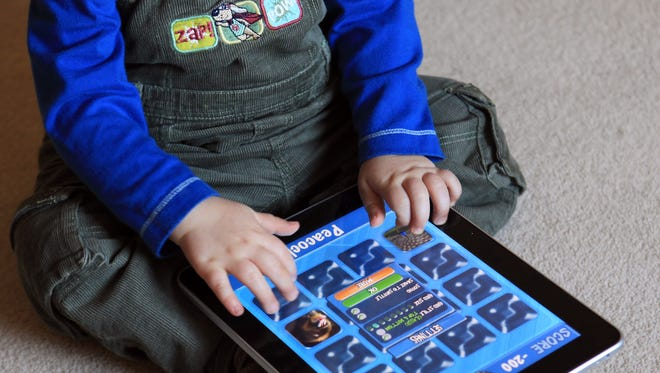 A 13-month old plays on a tablet.