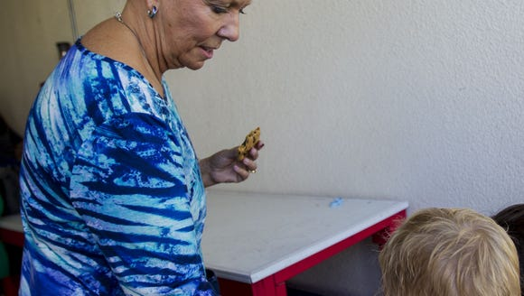 Christine Scarpati hands out cookies to children at