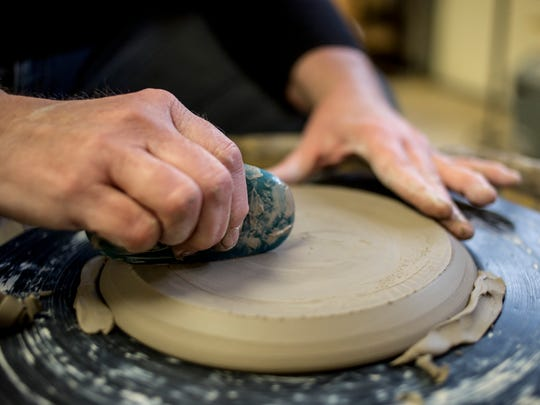 Deborah Maxwell trims a plate on the potters wheel