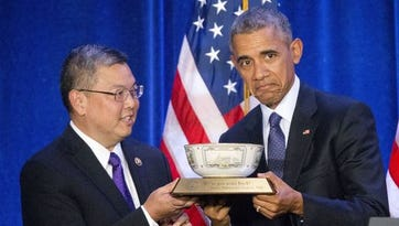 Rep. Mark Takai, D- Hawaii, presents President Barack Obama with a commemorative bowl before speaking at the House Democratic Issues Conference in Baltimore, Md., on Jan. 28, 2016.