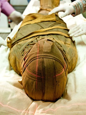 This undated photo provided by Dr Michael I. Miyamoto shows the mummified remains of Esankh, who lived in the third Intermediate period (1070-712 BCE), entering a CT scanner tube set up outside of the Egyptian National Museum of Antiquities in Cairo.