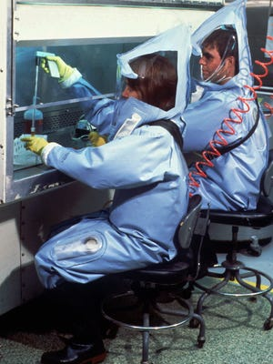 Researchers at the Centers for Disease Control and Prevention in Atlanta, Ga., are shown in in an undated file photo wearing protective lab suits like the ones used by personnel who worked with samples of the Ebola virus at the facility after an outbreak in Zaire in 1995.