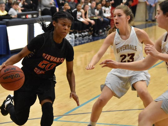 Stewarts Creek's Lauren Flowers drives to the basket as Riverdale's Jalyn Holcomb (23) and Allison Mayeux defend.