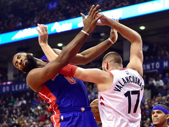 Toronto Raptors center Jonas Valanciunas (17) and Detroit Pistons center Andre Drummond (0) get tangled up under the net battling for a loose ball during the first half of an NBA basketball game in Toronto on Wednesday, Jan. 17, 2018.