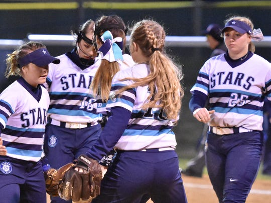 Siegel softball players gather near the pitcher's circle during a 2018 game. The Lady Stars went 32-3 last season.