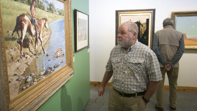 Richard Rosenberg of Elmhurst, Ill., looks at artwork at the Western Spirit: Scottsdale's Museum of the West in downtown Scottsdale on Tuesday.