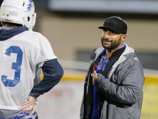 Agoura High head coach Kamran Salem talks with wide receiver Spencer Pearce during Wednesday's practice. After an 0-7 start, Agoura won its three league games and a first-round playoff game.