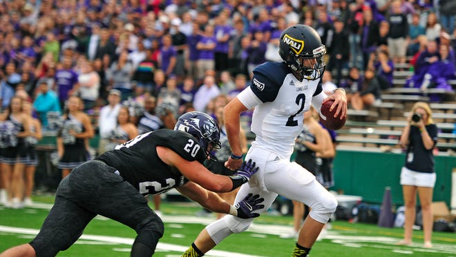 Northern Arizona University quarterback Kyren Poe (2) beats Abilene Christian linebacker Justin Stephens (20) to the end zone for a touchdown during an NCAA college football game, Saturday, Sept. 6, 2014, at Shotwell Stadium in Abilene, Texas.