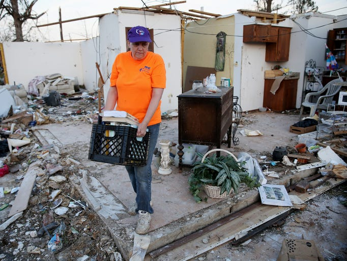 Penny Crowson salvages what she can from her home after it was destroyed by a tornado in Louisville, Miss.