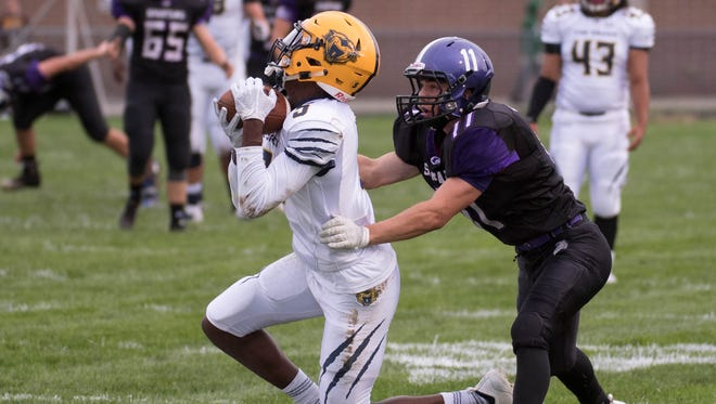 Battle Creek Central's Keondre Glass (5) gets an interception as Lakeview's Jackson Kitchen (11) goes for the tackle during first half action Friday evening.