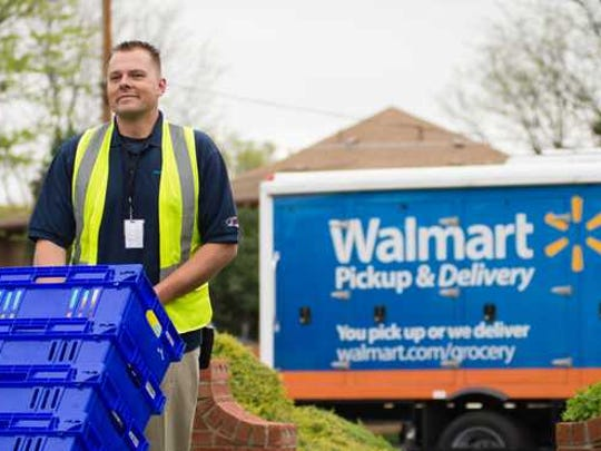 Walmart employee unloading blue totes from truck.