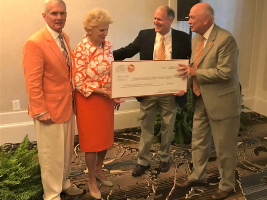 Clemson University President Emeritus James Barker and wife Marcia (left), along with Clemson University Foundation chief Hack Trammell (far right) accepted a scholarship fund donation Friday from Patrick Square developer/owner Michael Cheezem (second from right).