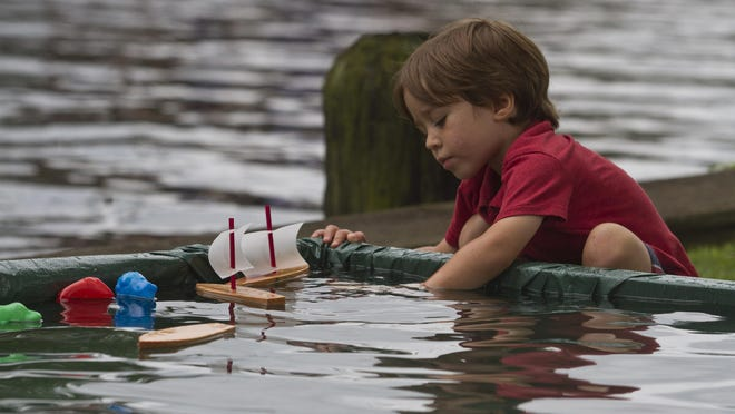 Silas Mickey, 3, of Toms River plays with toy wooden boats. Toms River Seaport Society and Maritime Museum holds the annual Wooden Boat Festival in Huddy Park downtown. Toms River, NJ Saturday, July 18, 2015 @dhoodhood