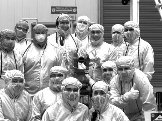 In September 2015, the Sample Camera takes a picture of the team that gave birth to it for its first light image after integration on the OSIRIS-REx spacecraft at Lockheed Martin in Denver. Christian d'Aubigny is pictured second from the left on the bottom row.