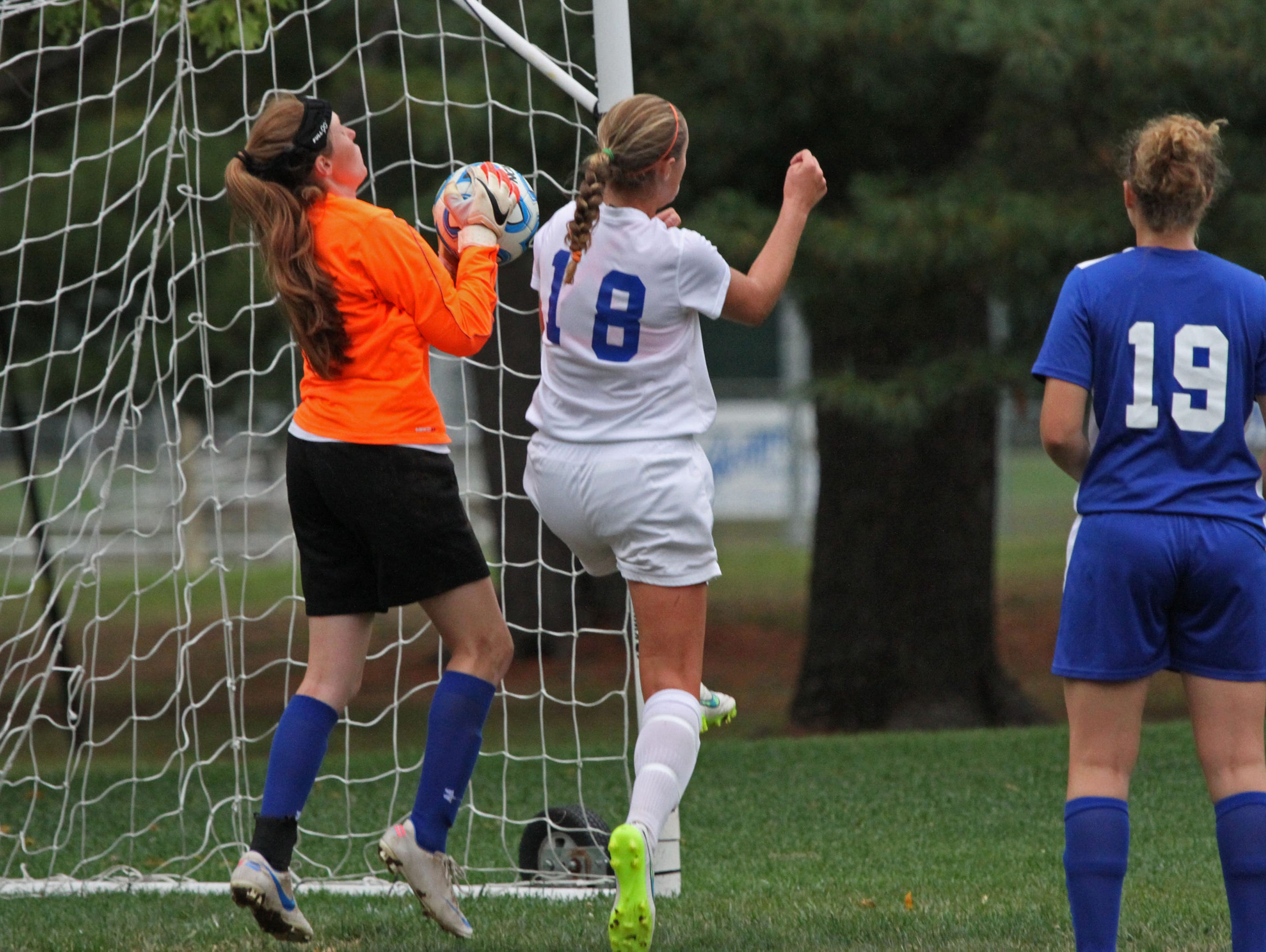 Metuchen goalie Emily Buchanan makes a save in girls soccer game at Middlesex. On offense is Mackenzie Meixner (18) for Middlesex.