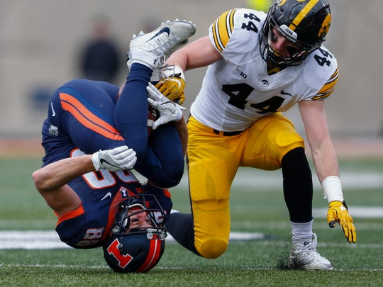 Zach Grant of the Illinois Fighting Illini cradles the ball in his legs that would eventually be called incomplete as Ben Niemann of the Iowa Hawkeyes defends at Memorial Stadium on Nov. 19, 2016, in Champaign, Ill.