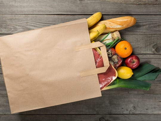 Different food in paper bag on wooden background, close