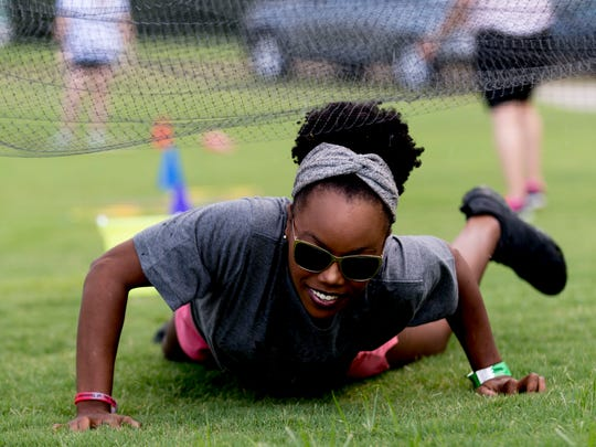 Lela Jackson, of Knoxville, crawls beneath a net in