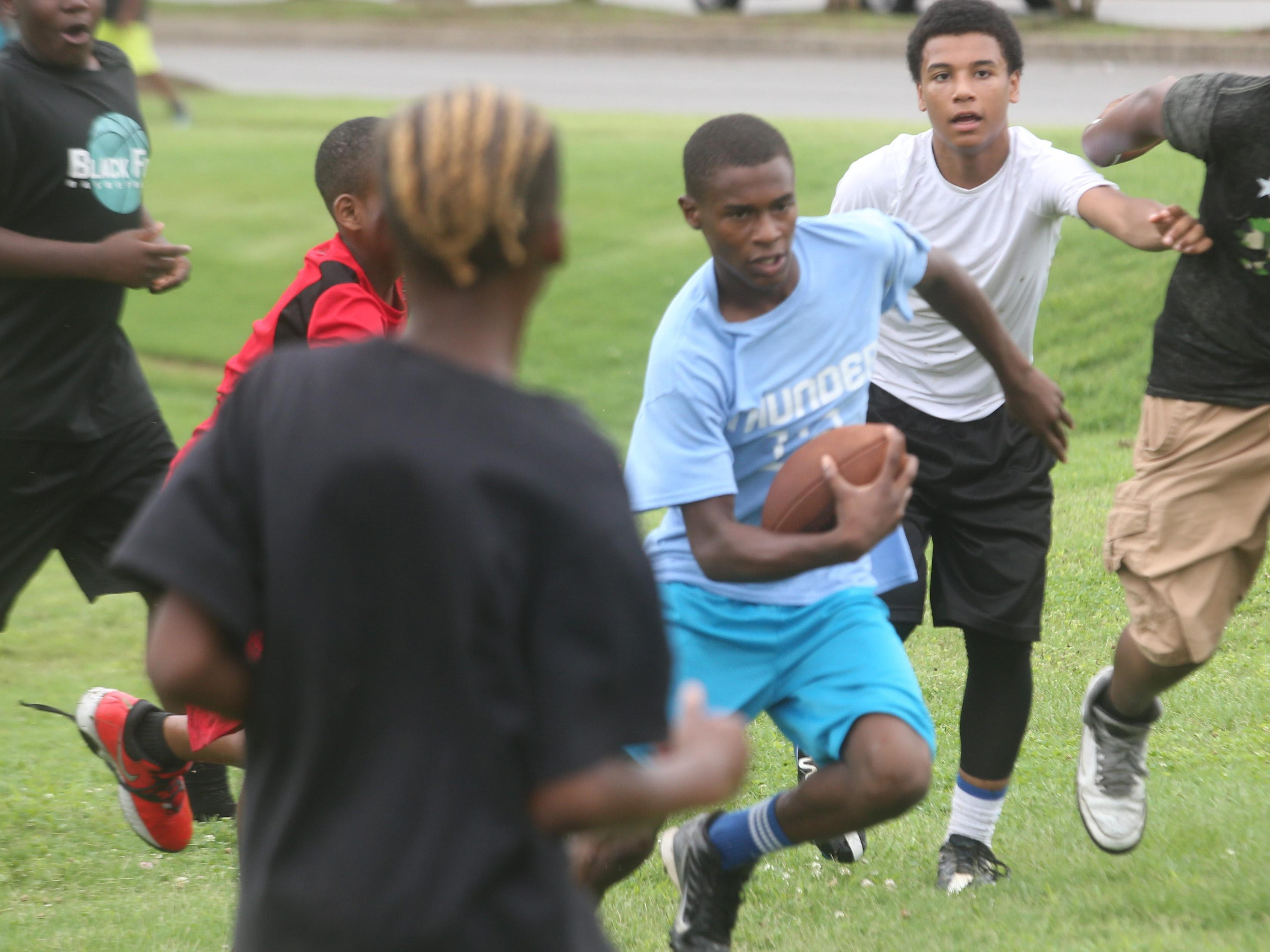 D'lando Spates runs with the ball during the 7-on-7 contest during Thursday's football camp.