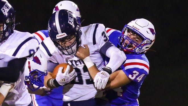 Winnacunnet's Dylan Atwood, right, wraps up Exeter's Jacob Wiberg during Friday night's football game in Hampton. The Warriors defeated the Blue Hawks, 16-13, in the season opener for both teams.