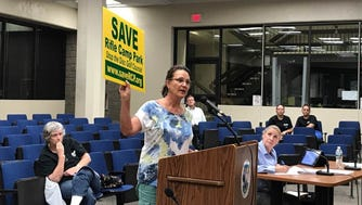Jeanette Luty, of Paterson, holds up a sign during the Woodland Park Council meeting Sept. 20. Luty encouraged residents to put signs on their lawns if they are opposed to the proposed disc golf course.