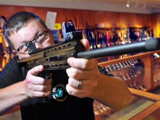 Doug Torpy of West Melbourne is a co-owner of Frogbones Family Shooting Center in Melbourne. He checks out the-hard-to-find Kel-Tec CMR-30 rifle.