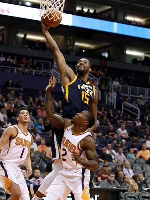 Utah Jazz center Derrick Favors (15) grabs an offensive rebound over Phoenix Suns' Eric Bledsoe (2) and Devin Booker during the first half of a preseason NBA basketball game Monday, Oct. 9, 2017, in Phoenix.