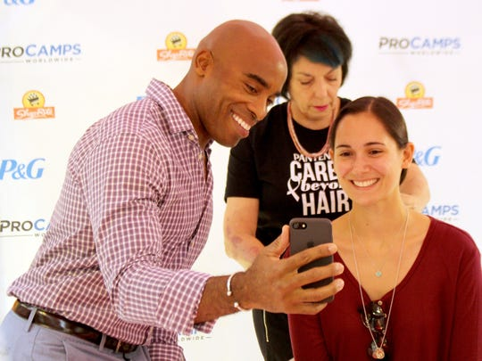 Retired football running back Tiki Barber captures the moment as Paige Garramone of Randolph, NJ gets her hair cut for Pantene's Care Beyond Hair campaign at the ShopRite of Greater Morristown. ShopRite customers donated their hair for the creation of real-hair wigs for women battling cancer.