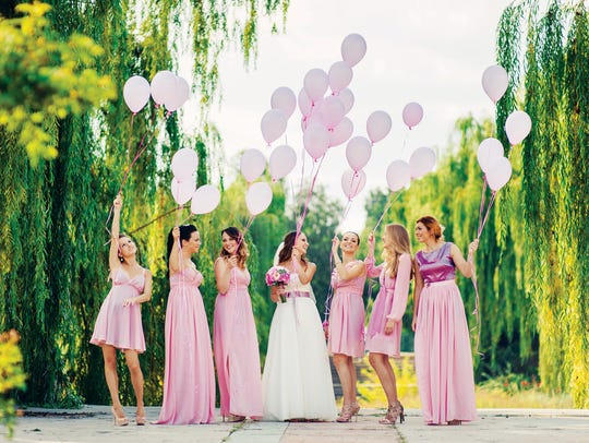 This bridal party are all wearing pink dresses in different