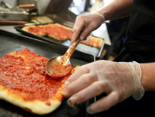 Manager Del Rill spreads sauce on a slice at DiCarlo's Pizza in York last year.