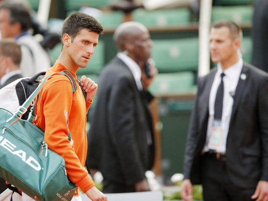 Serbia's Novak Djokovic leaves the court during his semifinal match against Britain's Andy Murray in the French Open tennis tournament at the Roland Garros stadium, Friday, June 5, 2015 in Paris. Djokovic and Murray have walked off center court in their French Open semifinal because of the threat of a rain storm. The play will resume Saturday. (AP Photo/Christophe Ena)