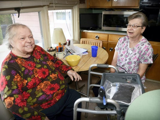 Patient Kay Cummings, left, is helped by Connie Brown. Brown's help, cooking and cleaning, helps Cummings stay in her home.