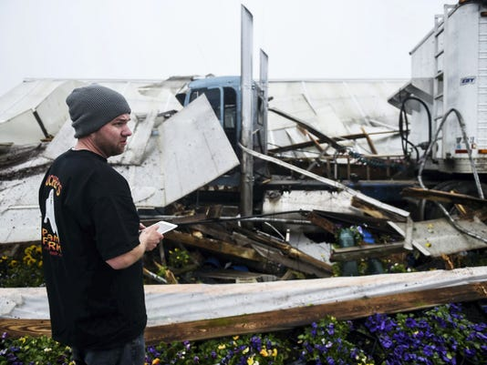 Jesse Auchey, with Auchey's Plant Farm, looks over damages caused after a tractor trailer crashed into a greenhouse at the West Manheim Township business during Friday's overnight hours.